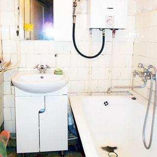 На фото: часть помещения ванной комнаты, прямо у стены в углу на тумбе белого цвета с дверцами - керамическая раковина со смесителем, над раковиной - зеркало, справа - ванная со смесителем, над ванной - газовая колонка, стены в половину высоты облицованы керамической плиткой