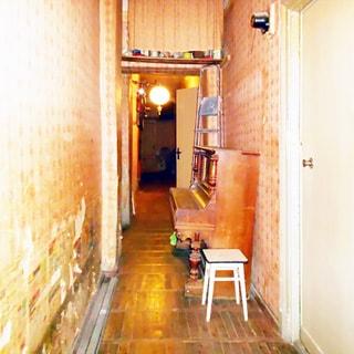 На фото: вытянутое в длину помещение коридора, слева - стена с обшарпаными обоями, справа двери в соседние помещения, слева от первой на стене - электросчетчик, справа у стены - пианино, под потолком - антресоль, закрытая шторкой, полы - паркет