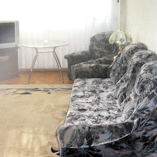 На фото: часть помещения жилой комнаты - гостиной, окно,  у окна - журнальный столик со стеклянной столешницей, слева от него - тумба с телевизором, справа от окна у стены - мягкое кресло, столик с настольной лампой, мягкий диван, полы - паркет, на полу - ковер