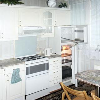 На фото: часть помещения кухни, окно, у окна - обеденный столик со стульями, слева от кона вдоль стены - комплект кухонной мебели из тумб-столов и навесных шкафов, двухккамерный холодильник, 4-комфорочная газовая плита с духовкой, над ней - вытяжка, фартук облицован керамической плиткой, на полу - ковер