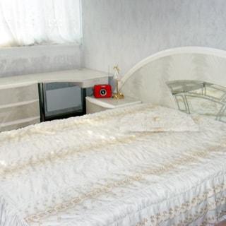 На фото: часть помещения жилой комнаты - спальни, окно, у окна - комод, туалетный столик, у стены - двуспальная кровать, слева от кровати - прикроватная тумбочка с ночником и будильником