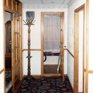 На фото: часть помещения прихожей, в центре, слева и справа - двери в соседние помещения, слева в углу вешалка - стойка для верхней одежды, над ней на стене - часы, стены оклеены обоями, на полу - ковер