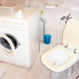 На фото: часть помещения санузла, подключенная стиральная машина с боковой загрузкой, унитаз - компакт с гигиеническим душем, полы и стены облицованы керамической плиткой