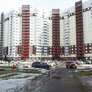 На зимнем фото: часть фасада 17-этажного многоквартирного жилого дома, застекленные балконы, открытые лоджии лестничных клеток, благоустроенная придомовая территория, газон, кусты, асфальтированные дорожки, детская площадка, припаркованные автомобили
