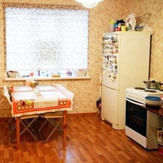 На фото: часть помещения кухни, трехстворчатое окно, у окна - обеденный стол с четырмя складными стульями вокруг него, справа от окна у стены - двухкамерный холодильник, справа от него - четырех комфорочная электрическая плита с духовым шкафом, стены оклеены обоями, полы - линолеум, на потолке - люстра