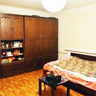 На фото: часть помещения жилой комнаты, слева вдоль стены - мебельная стенка с сервантом и одежным шкафом, справа у стены - разложенный диван, перед ним - журнальный столик, полы - линолеум, на потолке - люстра