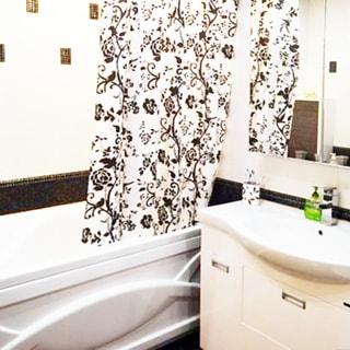 На фото: часть помещения ванной комнаты, прямо у стены в углу - ванная, спрва от нее - керамическая раковина на тумбе белого цвета с дверцами, над раковиной - шкафчик с зеркальными дверцами, стены облицованы керамической плиткой