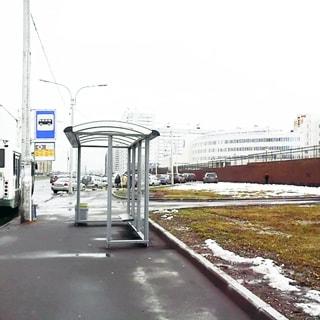 На зимнем фото: тротуар и автобусная остановка, справа от остановки - широкий газон, вдоль обочины проезжей части - припаркованные автомобили, на дальнем плане - жилые дома