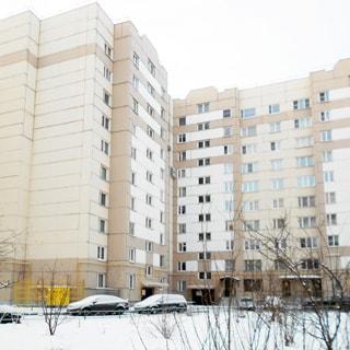На зимнем фото: часть фасада панельного десятиэтажного многоквартирного жилого дома, без балконов и лоджий, благоустроенная придомовая территория, огороженный газон, кусты, деревья, припаркованные автомобили, по фасаду на уровне первого-второго этажа проходит газовая труба желтого цвета