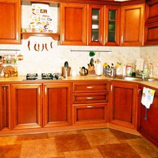 На фото: часть помещения кухни, встроенный кухонный гарнитур из тумб-столов с общей столешницей и навесные шкафы, в углу - металлическая мойка со смесителем, в левой секции - 4-комфорочная газовая варочная поверхность, над ней - вытяжка
