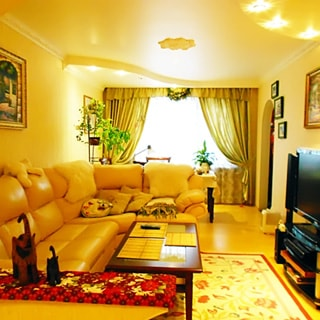 На фото: часть помещения жилой комнаты - гостиной, большое трехстворчатое окно, слева у стены большой мягкий диван с уголком, перед ним - журнальный столик, напротив у противоположной стены - тумба с телевизором, справа от окна - арка в соседнее помещение, на потолке - точечные светильники