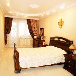 На фото: часть помещения жилой комнаты - спальни, трехстворчатое окно с балконной дверью, двуспальная кровать с подголовниками из массива дерева, слева и справа от кровати - прикроватные тумбочки, справа у окна - комод с зеркалом, на потолке - точечные светильники