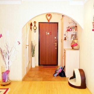 На фото: часть помещения просторной прихожей, по центру - входная металлическая дверь, справа от нее одежный шкаф и комод, слева - дверь в соседнее помещение, слева от двери на стене - трубка домомфона, полы - ламинат и плитка, стены оклеены обоями