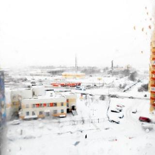 На зимнем фото: вид из окна через стекло во двор, во дворе двухэтажное административное здание с огороженной территорией, пешеходные дорожки и внутридворовые проезды, припаркованные автомобили