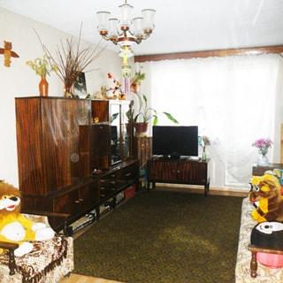 На фото: часть помещения жилой комнаты, трехстворчатое окно с балконной дверью, у окна - тумба с телевизором, слева от окна вдоль стены - мебельная стенка (сервант, шкаф, комоды, ящики), левее стенки - кресло, справа от окна у стены - диван, на полу ковер,  на потолке - люстра