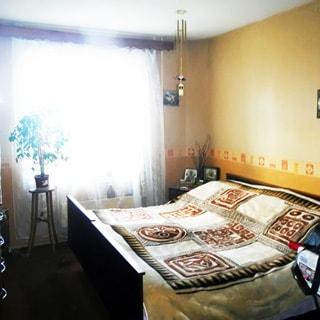 На фото: часть помещения жилой комнаты - спальни, двустворчатое окно, у стены - двуспальная кровать, слева от кровати - прикроватная тумбочка, у окна - высокая цветочная стойка, стены оклеены обоями