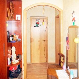 На фото: часть помещения коридора и прихожей, слева у стены - одежный шкаф, с боковыми открытыми полками, справа у стены - комод с зеркалом, слева от комода - стул, в центре впереди и справа деревянные двери в другие помещения