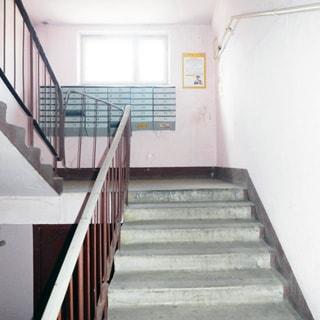 На фото: часть помещения лестничной клетки первого этажа, окно, под окном блок почтовых ящиков, лестница - бетонная, перила металлические с пластиковой накладкой, чисто и светло