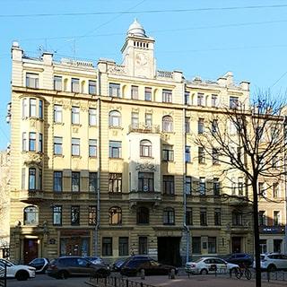 На фото: парадный фасад 6-этажного здания старой постройки, эркеры, башенка на крыше, проезжая часть прилегающих улиц с припаркованными автомобилями