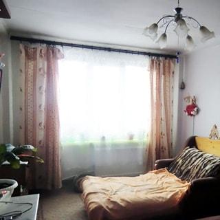 На фото: часть помещения жилой комнаты, большое трехстворчатое окно, под окном - радиатор центрального отопления, справа от окна у стены разложенный мягкий диван-кровать, над диваном - ночник, слева от окна у стены - тумбочка, на потолке - люстра, на полу - ковер