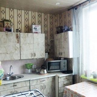 На фото: часть помещения кухни, окно, у окна небольшой обеденный столик, слева от окна вдоль стены - кухонный гарнитур, тумбы-столы и навесные кухонные шкафчики, металлическая мойка со смесителем, микроволновая печь, фартук облицован светлой керамической плиткой, слева у стены напротив окна - газовая плита, стены оклеены обоями, на потолке - точечные светильники