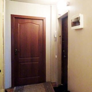 На фото: часть помещения прихожей, дверь в комнату, справа от нее - входная дверь в квартиру, слева от входной двери на стене - трубка домофона, справа от двери на стене - ящик с электрооборудованием, на полу - ковер