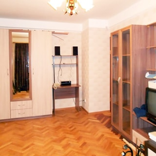 На фото: часть помещения жилой комнаты, прямо у стены - одежный шкаф с зеркальной дверью, в зеркале отражается окно, закрытое шторой, справа от шкафа - компьютерный столик, справа у стены мебельная стойка со шкафом со стеклянными дверцами, местом для телевизора, полками и комодом, стены оклеены обоями, полы - паркет