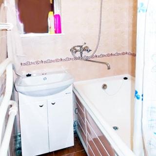 На фото: часть помещения ванной комнаты, прямо у стены в углу - керамическая раковина на тумбе белого цвета с дверцами, над раковиной - зеркало, справа - ванная, смеситель общий для ванны и раковины, стены облицованы керамической плиткой, полы - плитка