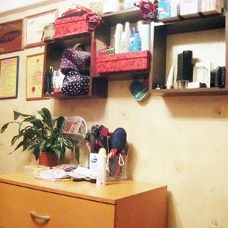 На фото: часть помещения жилой комнаты, стена, у стены - комод, над комодом на стене - полки, фотографии, дипломы, грамоты в рамках и без рамок, стена оклеена обоями