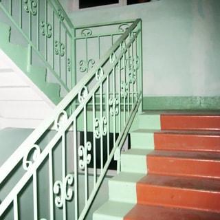 На фото: часть пространства лестничной клетки, металлические окрашенные перила, стены и ступени лестницы - окрашены, чистое и опрятное состояние, на межэтажных площадках - окна