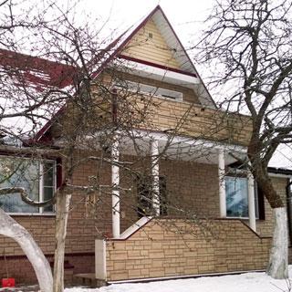 На фото: фасад загородного жилого дома с мансардой, высокое крыльцо, на д крыльцом на колоннах балкон мансардного этажа, фасад облицован декоративным фасадным камнем серого цвета, кровля - высокая, двускатная, окна - стаклопакеты, перед домом - деревья, зимнее время года, снег на крыше и перед домом