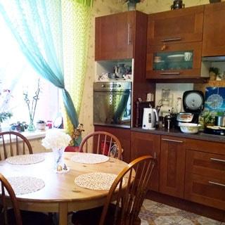 На фото: часть помещения кухни-столовой, окно, справа от окна вдоль стены - кухонный гарнитур со встроенной кухонной техникой, кухонная посуда, слева у окна - круглый обеденный стол со стульями, полы - плитка