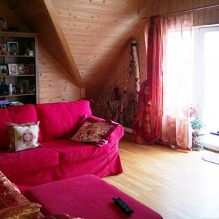 На фото: часть помещения жилой комнаты в мансардном этаже, большое окно с балконной дверью, мягкая мебель, стены обшиты деревянным сайдингом, полы - ламинат