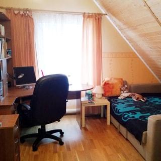 На фото: часть помещения жилой комнаты в мансардном этаже, окно, справа от окна - диван-кровать, слева от окна - письменный стол-секретер, мягкое офисное кресло на колесиках, приставная тумба письменного стола, стены обшиты деревянным сайдингом, полы - ламинат