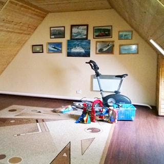 На фото: часть помещения комнаты в мансардном этаже, без мебели, на полу - ковер, на ковре - велотренажер и детские игрушки, справа падает свет от окна, на стене - фотографии и эстампы, своды и потолок обшиты деревянным сайдингом