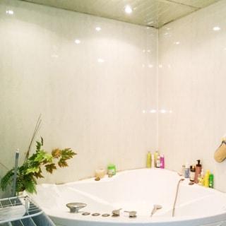На фото: часть помещения санузла с большой угловой ванной типа джакузи, на потолке - точечные светильники, стены и потолок облицованы сайдингом