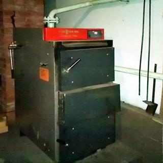 На фото: часть хозяйственного помещения, на полу установлен газогенераторный котел Viessmann на древесном топливе