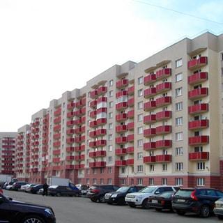 На фото: часть фасада 10-этажного многоквартирного жилого дома, новый чистенький фасад, балконы, асфальтированная дворовая придомовая территория, припаркованные автомобили
