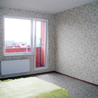 На фото: часть помещения жилой комнаты, окно с балконной дверью, установлен стеклопакет, под окном - батарея центрального отопления, слева у стены - двуспальная кровать, стены и пол облицованы древесно-волокнистой плитой