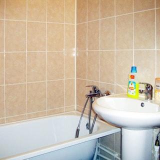 На фото: часть помещения ванной комнаты, керамическая раковина на стойке, со смесителем, слева от раковины - ванная со смесителем, стены облицованы керамической плиткой бежевого оттенка