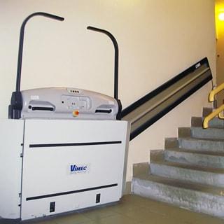 На фото: часть помещения лестничной клетки первого этажа, пролет лестницы до лифтового холла оборудован электроподъемником колясок для людей с ограниченными возможностями, полы облицованы керамической плиткой, стены окрашены