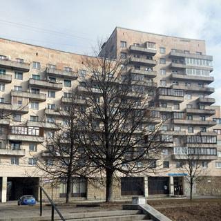 На фото: фасад многоквартирного жилого дома, часть здания - 8 этажей, вторая часть здания - 11 этажей, высокий цокольный этаж нежилого назначения, балконы по фасаду, арка во двор, благоустроенная придомовая территория - газон, деревья, тротуар, проезжая часть, припаркованный автомобиль
