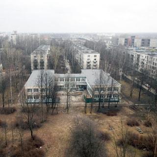 На фото: вид из окна во двор, во дворе - сквер, газон, деревья, типовое двухэтажное здание детского сада, за ним - панельные пятиэтажные жилые дома