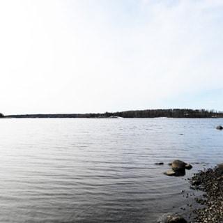 На фото: вид с берега на водную гладь и противоположный берег, на переднем плане справа видна часть берега - галька, противоположный берег - лесной
