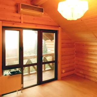 На фото: часть комнаты мансардного этажа, большое трехстворчатое окно полной высоты с выходом на балкон, стеклопакет, над окном - кондиционер, слева у окна - радиатор отопления, стены - доска, блок-хаус или оцилиндрованное бревно, полы - ламинат, без мебели, на потолке - люстра