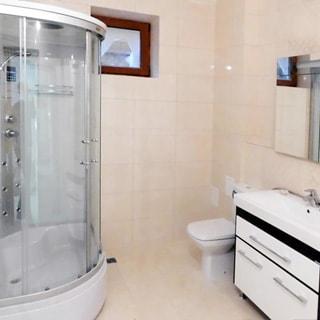 На фото: часть помещения совмещенного санузла, небольшое окно, слева - душевая кабина, справа - унитаз, раковина на тумбе, смеситель, над раковиной - зеркало, полы и пол - плитка бежевого цвета