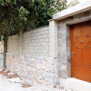На фото: часть ограждающего каменного забора выше человеческого роста, вход на участок закрыт металлической дверью, за забором - зеленая растительность, деревья