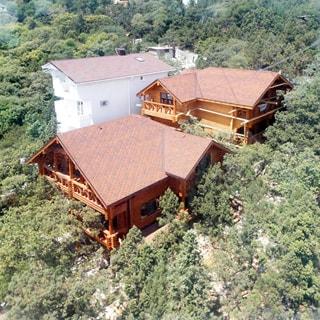 На фото: вид на дом и учаток с высоты, дом утопает в зелени деревьев, за домом из дерева - дом из белого камня, за ним все утопает в зелени деревьев, других построек за деревьями не видно
