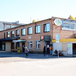 На фото: фасад кирпичного двухэтажного здания административного типа, с правой стороны - пристройка из профилей, с фасада - вход в почтовое отделение, вход в ломбард, плоская кровля, окна - стеклопакеты, перед зданием - асфальтированная территория для пешеходов и стоянки автотранспорта