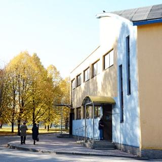 На фото: часть фасада двухэтажного здания административного типа, стены оштукатурены, с фасада - два входа, один - под козырьком с пандусом и ступеньками, второй - с наружной винтовой лестницей на второй этаж, окна - стеклопакеты, перед зданием тротуар вымощен камнем, проезжая часть асфальтирована, за ней - газон, деревья